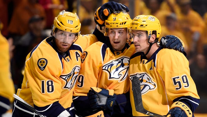 Nashville Predators right wing James Neal (18) and left wing Filip Forsberg (9) celebrate the first-period goal by defenseman Roman Josi (59) at Bridgestone Arena Friday, Oct. 14, 2016, in Nashville, Tenn.