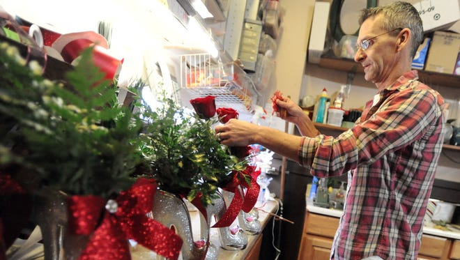 Ryan Elliott of Fuzzy's Flowers & Gifts, 297 Mount Vernon Ave., puts together several Cinderella bouquets Monday for Valentine's Day, which is Saturday.