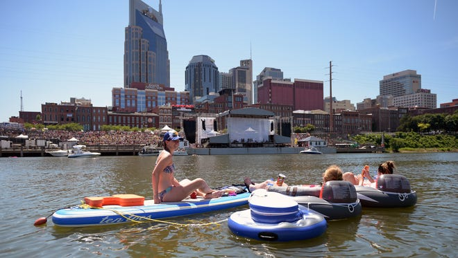 Jessica Richmond, Valerie Boschloo and Lindsay Boyer float on the Cumberland River across from Riverfront stage during the CMA Music Festival on Friday, June 10, 2016.