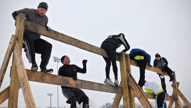 Contestants climb an obstacle during Saturday's Iceman Extreme Obstacle Course 5K at the Granite City Speedway in Sauk Rapids.