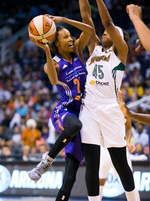Mercury forward DeWanna Bonner goes to the basket as Seattle Storm guard Noelle Quinn defends during the first half in the WNBA opener at the US Airways Center in Phoenix on Saturday, May 17, 2014.