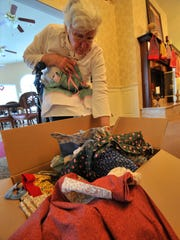 Resident Phyllis Lubbe, 78, looks through fabrics that can be used to sew dresses.