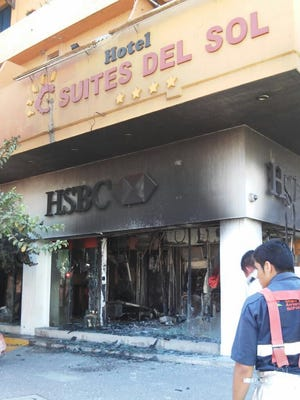 Firefighters work to put out a fire May 1, 2015, in a bank in Puerto Vallarta, Mexico. Criminals burned gas stations and 4 banks that day.