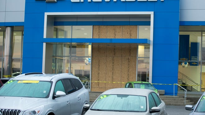 A boarded front window stands at Bill Estes Chevrolet on West 96th Street in Indianapolis after a car thief blasted through the showroom glass Wednesday night driving an Indy 500 pace car.