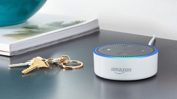 An Amazon Echo Dot sits on a counter next to a set of keys.
