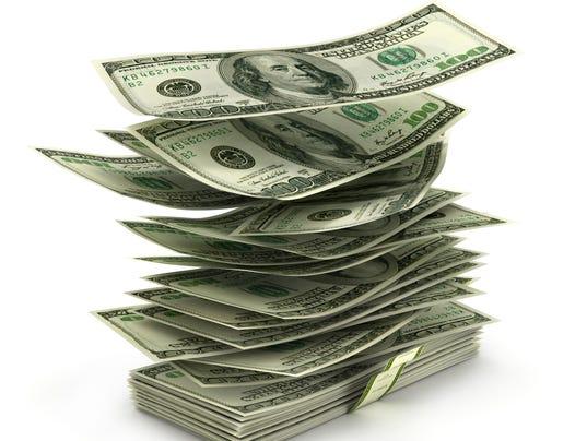 flying dollar bills in stack
