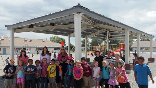 Yerington Elementary School students and YES PTO board members stand in front of the new shade structure funded by PTO. The board members (back, from left), Bonnie Bobrick, Anna Draper, Heather Cooper and Shannon Coombs are joined by Financial Horizons Credit Union representatives Micaela Garcia and Ada Willingham.