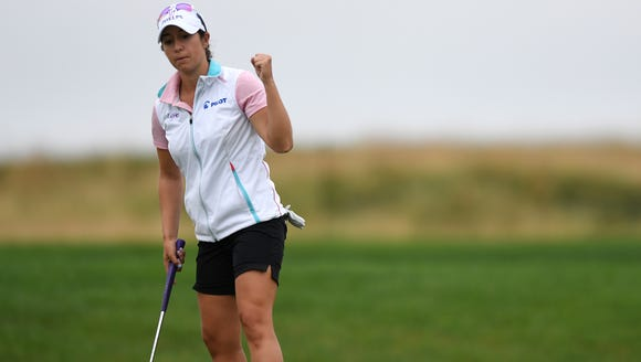 Marina Alex celebrates after sinking a put on the 15th
