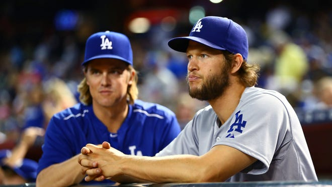 Dodgers pitchers Zack Greinke, left, and Clayton Kershaw watch a game at Chase Field.