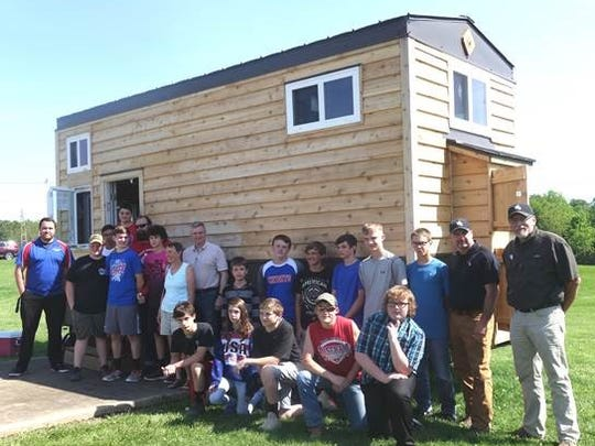 Standing in front of the tiny house project are  (front row left to right) Cooper Charlton (middle school teacher), students Zach Shaner, Dillion Miller, Gage Marmot,  Mrs. Coleman, (kneeling) students Conner Varnes, Katie Stitzlein, Brody Allen, Drake Mullet, Curtis Cutright. Back row:  students Dylan Strouse, Dodge Raber, Dave McMillen (Building Trades instructor), Mr. Coleman, students Damion Torrence, Brock Zimmerly, Tucker Kaufman, Logan Barlow, Blake McCombs, Rudy Hershberger and auction team Tim Miller and Dan Miller of Kaufman Reality.