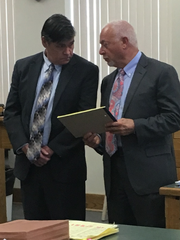 Michael J. Phillips confers with defense attorney Kelley