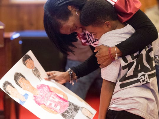 "Xavier Fletcher is hugged by Zenobia Dobson after he presented her with a drawing of her son, Zaevion Dobson during the ""Remembering Our Hero: Zaevion Dobson"" service at First Calvary Baptist Church on Saturday, Dec. 17, 2016. Saturday marked the one-year anniversary of Zevion Dobson's death."
