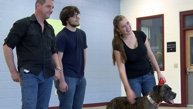 From left, Lloyd Goldston and his children are reunited with their dog, Boozer, after a 9-year separation, in Golden, Colorado. Boozer, now 10, went missing while the family was moving from Tennessee to Alabama.