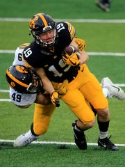 Nick Niemann tackles Max Cooper during open practice at Kinnick Stadium Friday, April 20, 2018.