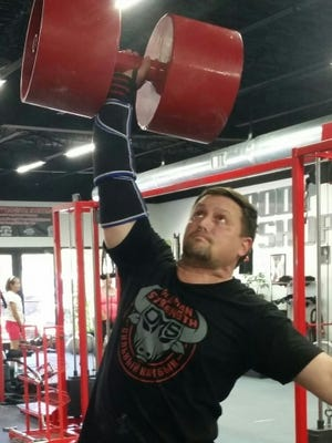 Jake Benth, the event organizer, lifts a circus dumbbell.
