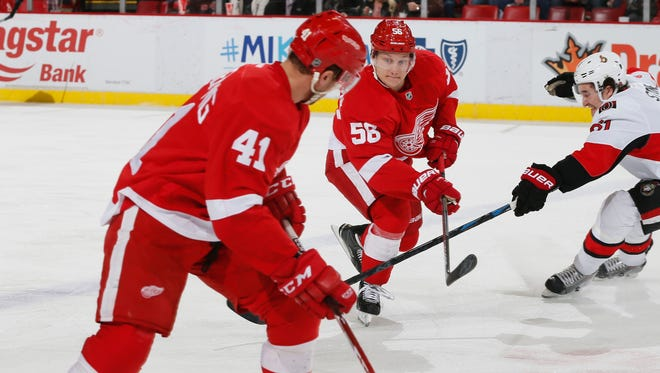 Detroit Red Wings Teemu Pulkkinen, center, pass to the puck to Luke Glendening as he skates against the Ottawa Senators Mark Stone in the first period on Tuesday, March 31, 2015 in Detroit.