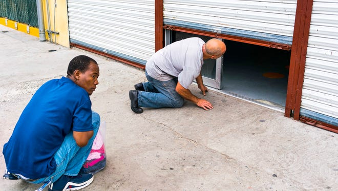 A Haitian migrant peers under the door of Desayunador Salesiano Padre Chava, a shelter for migrants in Tijuana. The shelter was closed and the man had knocked on the door hoping to get some food.