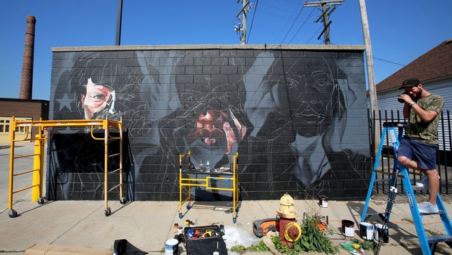 Elliot O'Donnell takes photo by the mural he and Sydney G. James are working on in unusual hot weather for September at Murals in the Market in Detroit, Michigan, Saturday, September 23, 2017.