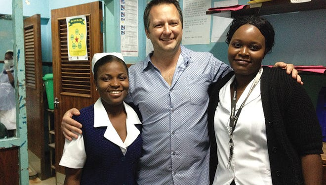 Dr. Joseph Fulton (center) poses with two of his nurses while teaching and providing care during a trip to Malawi in 2015.