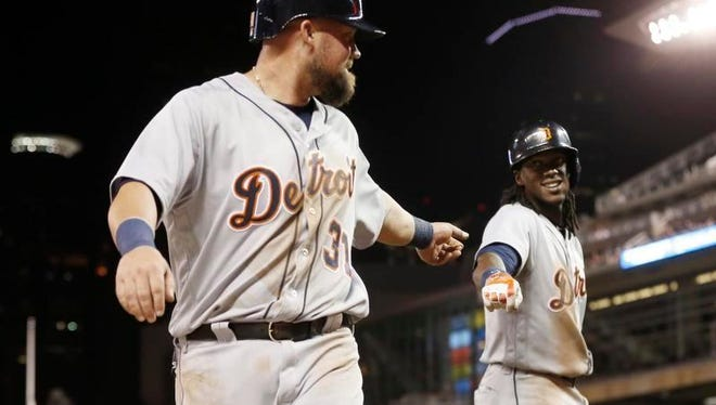 Detroit's Casey McGehee, left, is congratulated by Cameron Maybin after McGehee scored on a two-run single by Andrew Romine in the eighth inning against the Twins Wednesday.