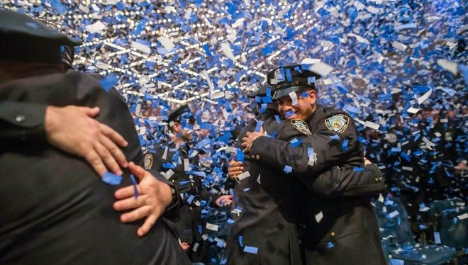 The newest members of the New York City police force hug during their graduation ceremony, Thursday, June 29, 2017, in New York. New officer Michael Velazquez, a Yonkers resident, proposed to his girlfriend after the ceremony at Madison Square Garden.