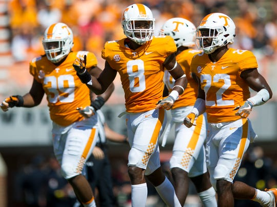 Tennessee defensive players run off the field during Tennessee's game against UMass in Neyland Stadium on Saturday, Sept. 23, 2017.