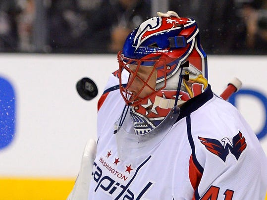 Washington Capitals goalie Jaroslav Halak, of Slovakia, deflects a shot off his mask during the second period of an NHL hockey game against the Los Angeles Kings, Thursday, March 20, 2014, in Los Angeles. (AP Photo/Mark J. Terrill)