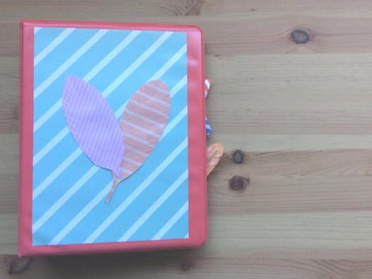 Scrapbook paper and feathers add interest to a binder with a plastic sleeve.