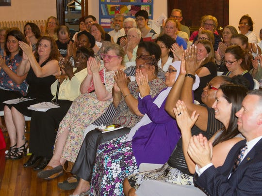 Members and supporters of the Speakers Bureau applaud during a graduation speech.