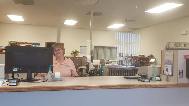 Pratt city office manager Angie Branscom works with new safety standards, including a plastic shield between customers and office personnel, at the city office, which is now open to the public.
