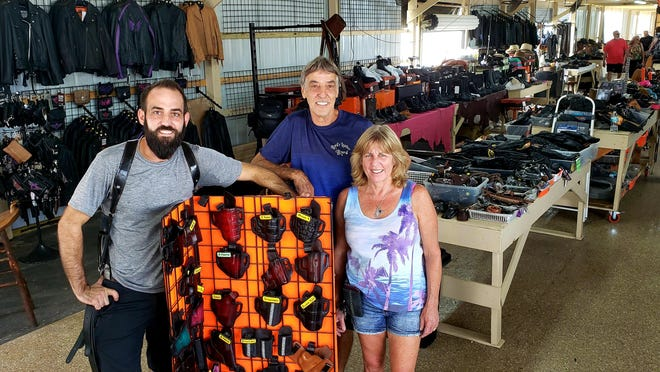 Steven Travis and his parents, Byrd and Kathy Travis, are all smiles in their new location on row D at the Daytona Flea & Farmers Market on Saturday, June 27, 2020. The move comes three weeks after their business, Byrd's Custom Leather, sustained significant damage during a storm.