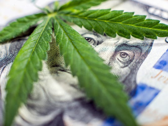 A marijuana leaf on top of a $100 bill