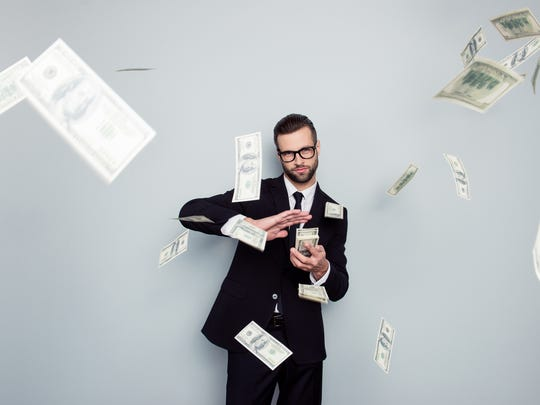A man flicking money into the air