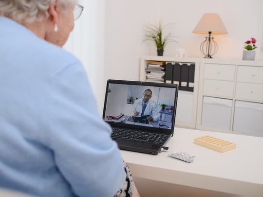 An elderly woman videoconferencing with a doctor on a laptop using a telehealth platform.