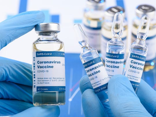 Gloved hands holding coronavirus vaccine bottles