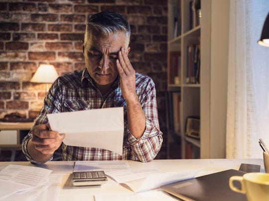 Older man at desk holding head while reading document