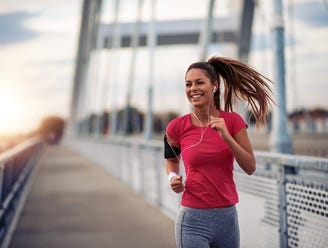 A woman jogging over a bridge.