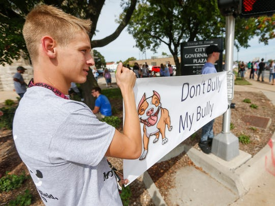 """Austin Jennings, 16, left, and Nikkolas Korth, 18, hold up a sign during the """"Don't Bully My Bully"""" rally in front of city hall on Friday, August 25, 2017."""