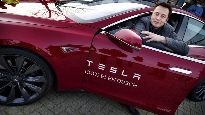 CEO Elon Musk, co-founder and CEO of American electric vehicle manufacturer Tesla Motors, poses with a Tesla during a visit to Amsterdam on Jan. 31.