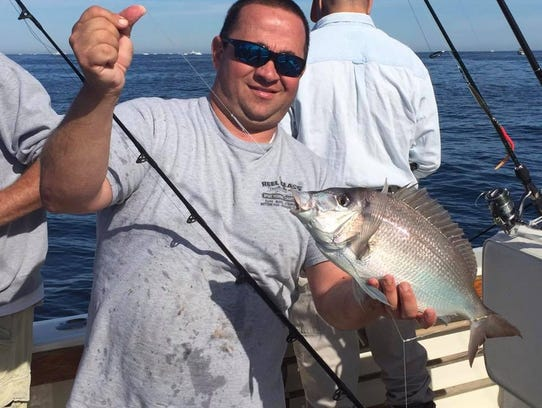 Captain Allen Gonzalez of the Reel Class charter boat with a porgy landed on the boat's Sunday, Oct. 22, 2017, trip.