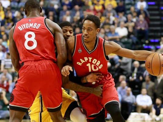 Toronto Raptors DeMar DeRozan, right, drives with the basketball while Raptors center Bismack Biyombo, left, screens Indiana Pacers forward Paul George, center, in the first half of an NBA basketball game, Monday, Dec. 14, 2015, in Indianapolis. (AP Photo/R Brent Smith)