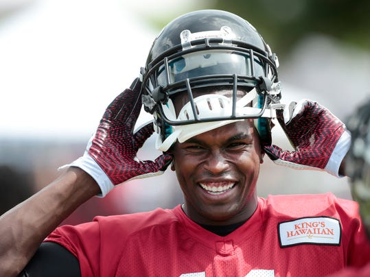 Atlanta Falcons wide receiver Julio Jones puts his helmet on as he prepares for an NFL football training camp Friday, July 25, 2014, in Flowery Branch, Ga. (AP Photo)