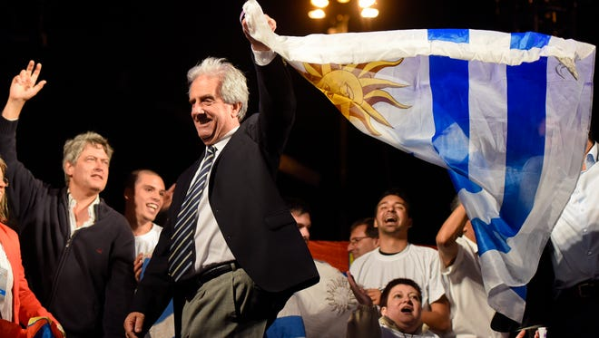 Uruguay's President elect Tabare Vazquez waves flag to celebrate his victory.