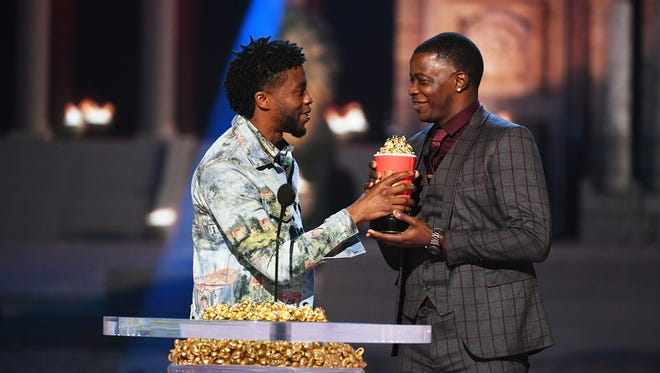 Chadwick Boseman (left) presents his trophy to James Shaw Jr. during the MTV Movie And TV Awards on June 16, 2018, in Santa Monica, California.