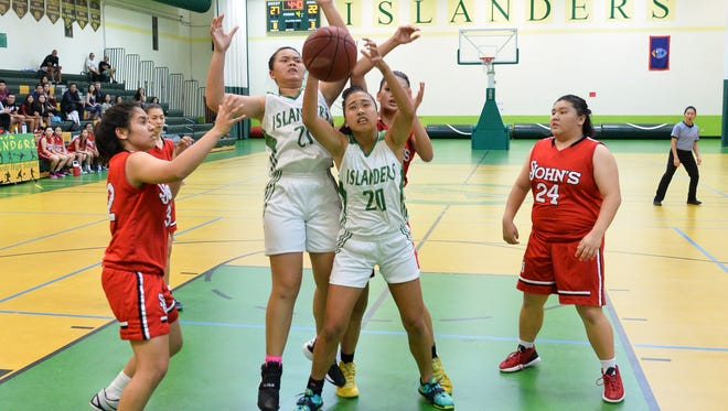 Players fight for a rebound in an Independent Interscholastic Athletic Association of Guam Girls Basketball League match between the John F. Kennedy Isladers and the St. John's Knights at JFK on Nov. 22, 2016.