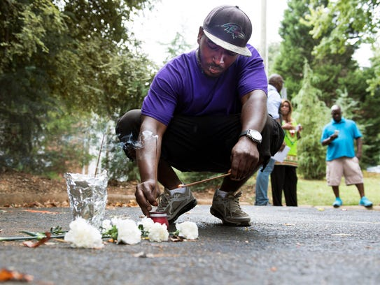 Jermaine Hicks lights a candle at a small memorial