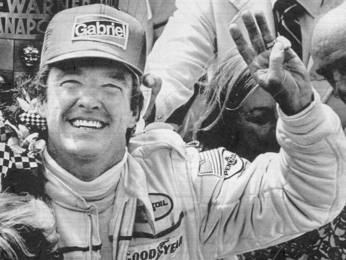 Johnny Rutherford holds up three fingers to indicate