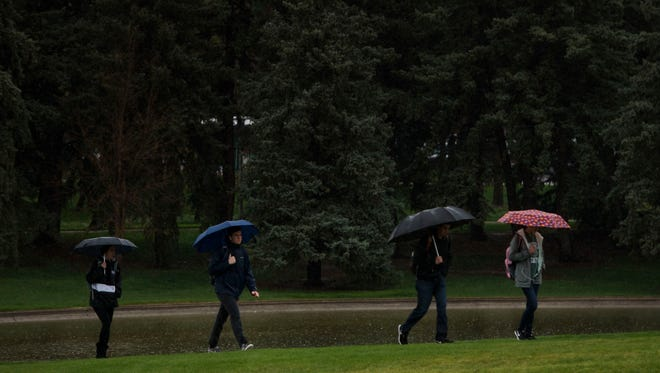 Students walk through the rain on Thursday, May 3, 2018, on CSU's campus in Fort Collins, Colo.