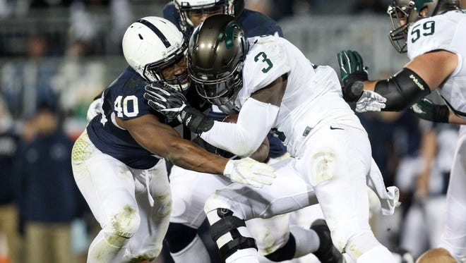 Nov 26, 2016; University Park, PA, USA; Michigan State Spartans running back LJ Scott (3) runs with the ball as Penn State Nittany Lions linebacker Jason Cabinda (40) blocks during the third quarter at Beaver Stadium. Penn State defeated Michigan State 45-12.