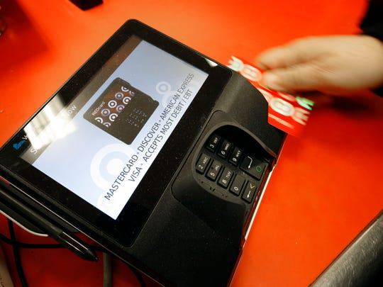 A shopper pays for her purchases Nov. 28 at a Target store in South Portland, Maine. Criminals stole personal information from tens of millions of Americans in data breaches in 2014. Of those affected, one in three became victims of identity theft, according to research firm Javelin.